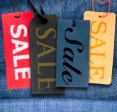 11879070-tags-with-sale-sign-with-stack-of-blue-jeans-in-background